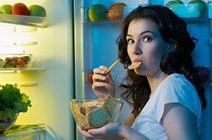 woman eating food in front of fridge