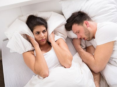 woman trying to sleep next to snoring man